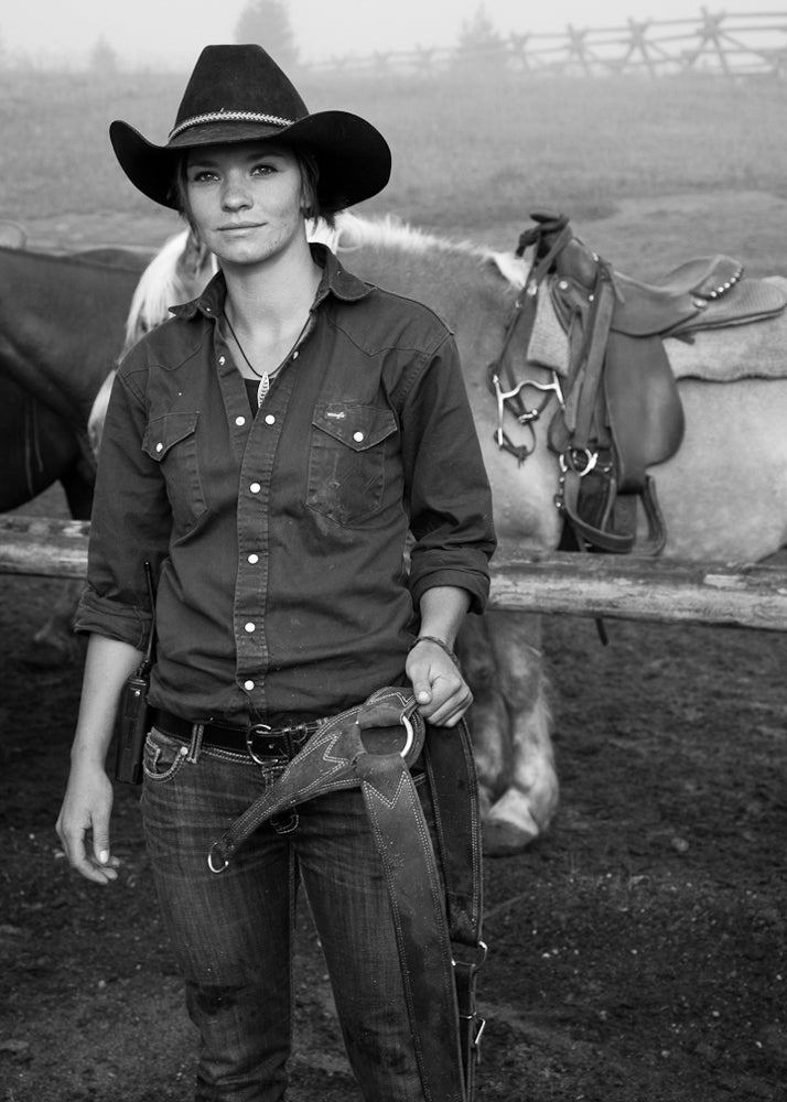 Stacy stands in the Canyon horse corral, where wranglers prepare 50 to 60 horses a day for trail rides in Yellowstone National Park.