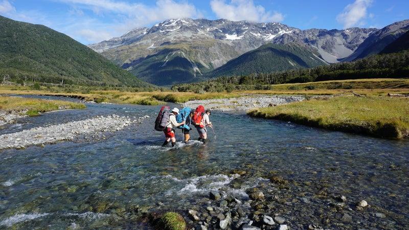 Hiking partners cross a stream near Nelson Lakes, New Zealand.