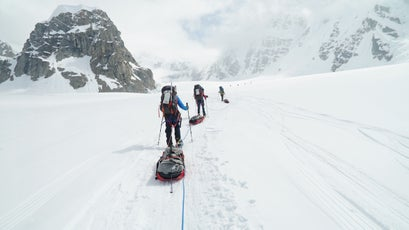 Lucy and her team walking with gear up Denali.