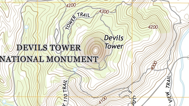 """And here is Devil's Tower on a proper USGS topo map. You can immediately see how much more information is available, describing even hitherto unseen terrain features surrounding the butte, which rises steeply in the middle of the map. The farther apart the contour lines, the more gradual the slope; the closer they are, the steeper the slope. As you can see in the photograph up top and on this topo map, Devil's Tower rises almost vertically. On this map, the contour interval is 20 feet, meaning each line is 20 vertical feet from the next one. You can see valleys formed by contour lines making a """"V"""" pointed uphill, while ridges make a """"V"""" pointed down. Peaks are represented by rough circles, as on Devil's Tower."""