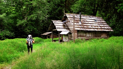 A hiker approaches the Olympus Ranger Station along the Hoh River trail.
