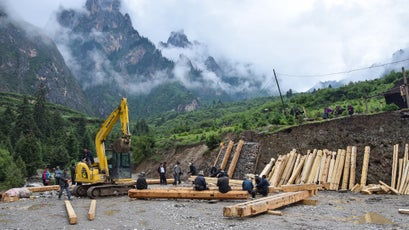 Local construction crews work to upgrade Zhagana's dirt parking lot, located at the base of the village.