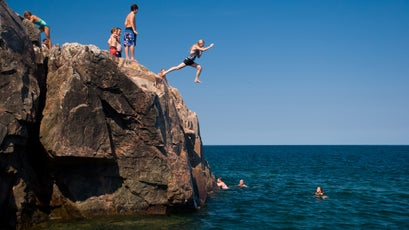 A girl jumps into Lake Superior from the rocky shore of Little Presque Isle in the Upper Peninsula of Michigan.