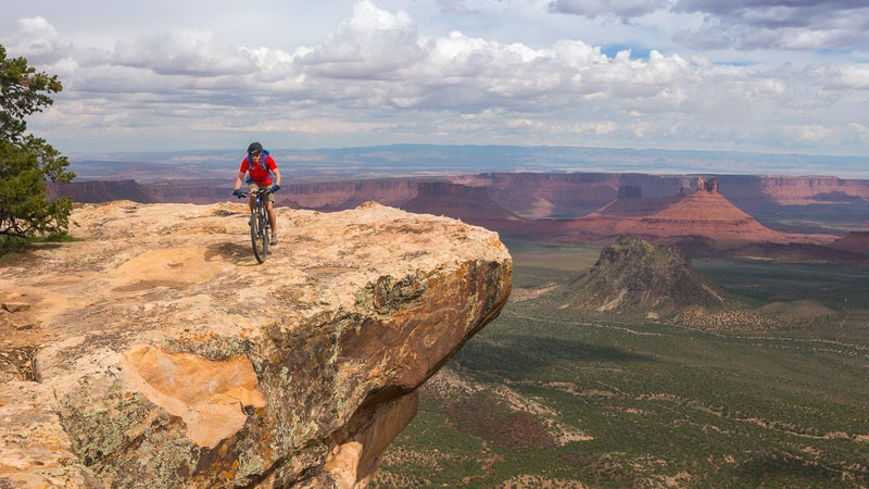 A mountain biker riding above Castle Valley on the Porcupine Rim Trail near Moab, Utah.