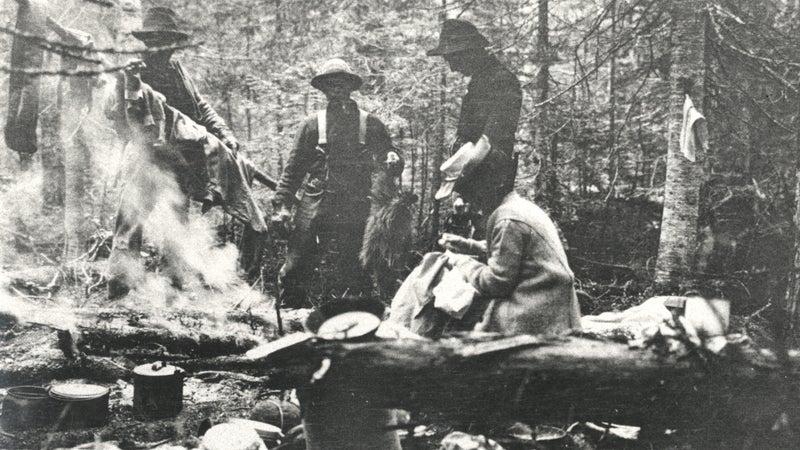Mina Hubbard and three men around campfire, 1905.