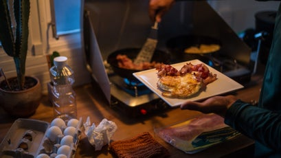 Josef Sipiorski makes breakfast inside the renovated 1965 Streamline Countess camper that he shares with his brother on the north end of Jackson, Wyoming. The two work as lifeguards at the recreation center and, like others at the camp, have their parking fees covered for the summer.