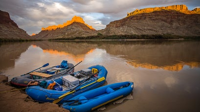 Rafts sit anchored to the shore of the Colorado river at Spanish Bottom as the sun sets on the peaks behind, Canyonlands National Park, Utah. Photo taken during a raft trip down the Colorado river from Moab to Lake Powell through Canyonlands National Park and Cataract canyon, Utah.