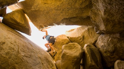 Russell Moore climbs through an open ended granite boulder cave in Anza Borrego State Park. California