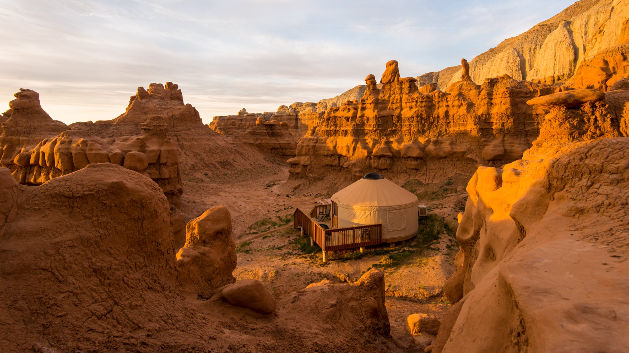 Sunrise hits a yurt below the red-rock cliffs of Goblin Valley.