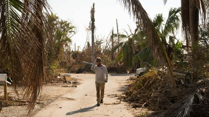 Will Benson walks between piles of debris after clearing a property.