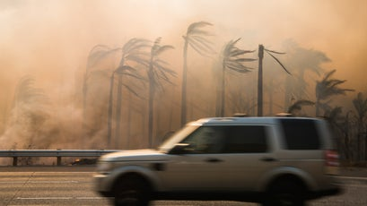 A motorist dives south on the 101 Freeway as the Thomas Fire burns between the roadway and the Pacific Ocean near Carpinteria, December 7, 2017.
