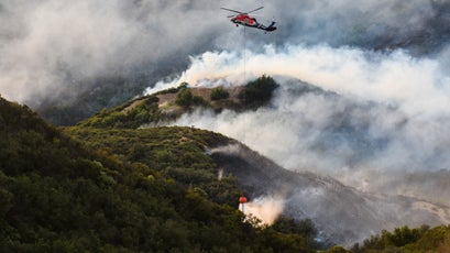 A privately contracted helicopter drops a bucket of water on the Thomas Fire in Los Padres National Forest near Ojai, December 9, 2017.