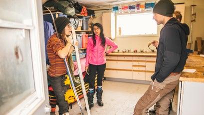 Sarah McNair-Landry (left) talks with Lin, Jonatan, and Eddie (hidden) in Matty's workshop early in training.