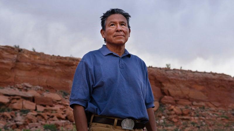 Mark Maryboy standing in red sand desert