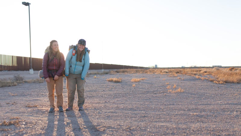 Claire Wernstedt-Lynch and Tenny Ostrem share a light moment near the border wall in Columbus, New Mexico, in January.
