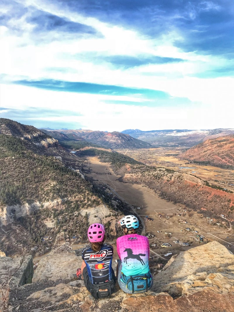 Aleah Austin (left) and Tina Ooley sitting near the shrine they built for Tricia Shadell outside Durango, Colorado.