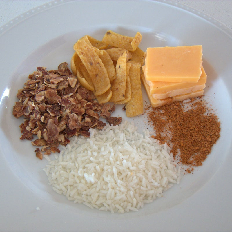 Clockwise from cheese in upper right: Cheese, taco seasoning, rice, refried beans, and Fritos