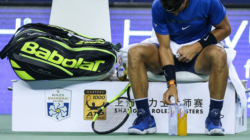 Tennis player Rafael Nadal meticulously arranges his bottles during a match.