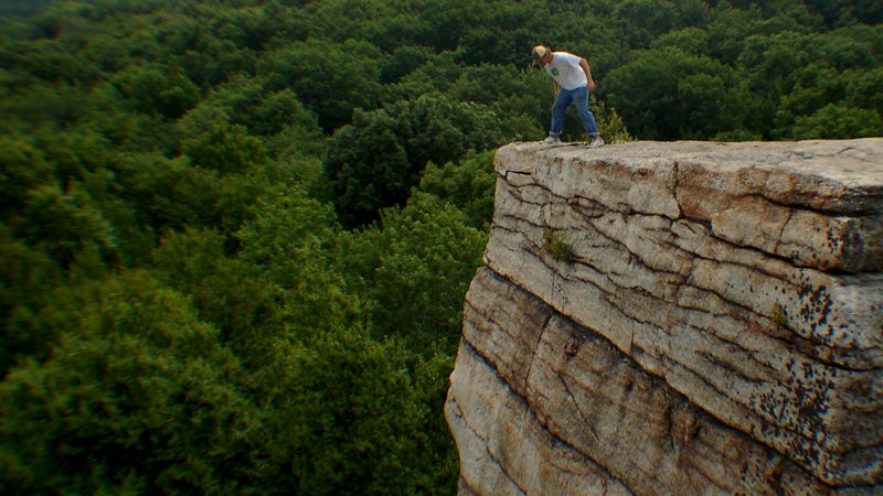 A hiker looks over a cliff in the Shawangunks.