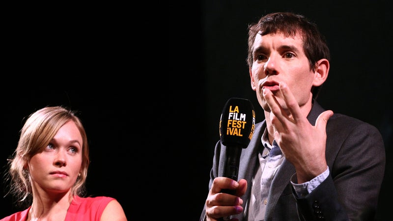 """Sanni McCandless watches Alex Honnold, or perhaps his hands, as they speak onstage at a """"Free Solo"""" screening."""