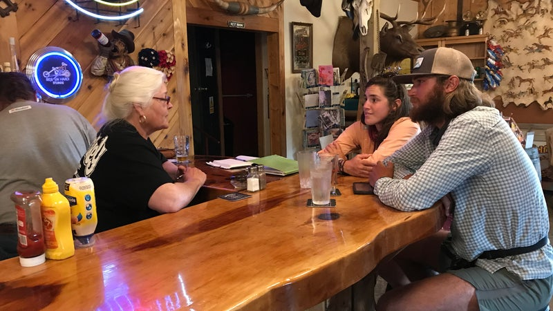 Laurel Nelson, co-owner of Miner's Grubstake and Dredge Saloon, with two thru-hikers.