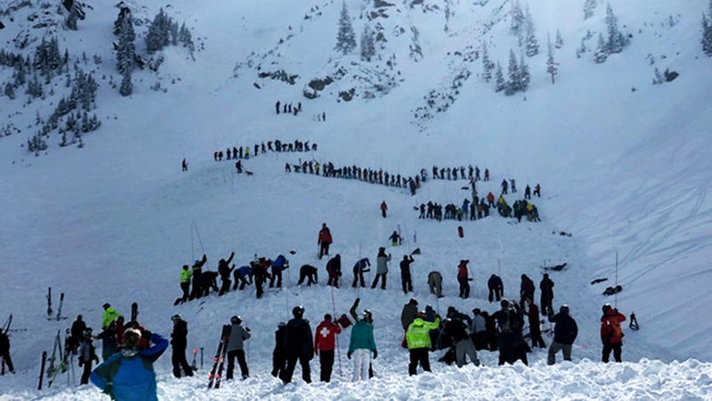 Rescuers form lines to probe for people buried in an avalanche at the bottom of Kachina Peak on Thursday.