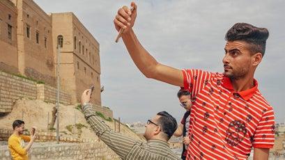 Iraqi men take selfies.