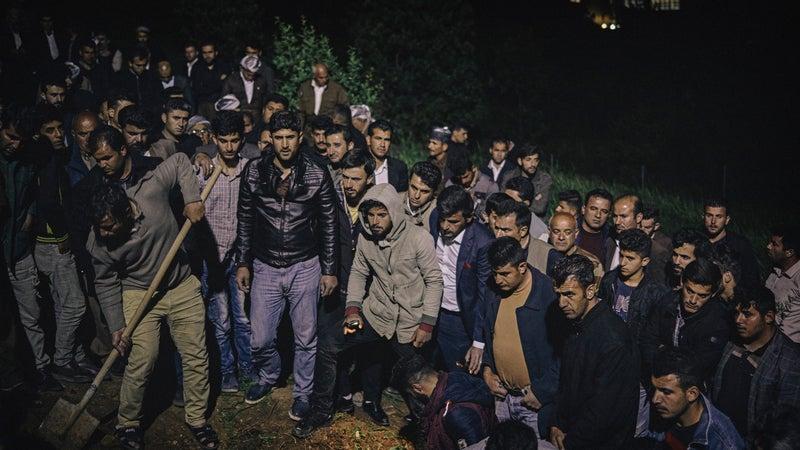 Kurdish men attend the funeral of landmine victim Haidar Shwan.