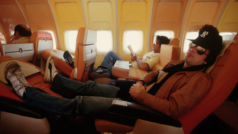 Billy Joel reclines on a flight during a tour
