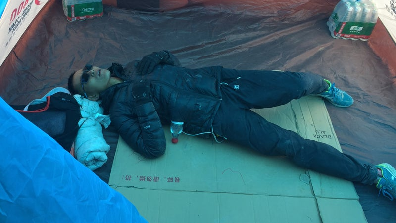 Liang Jing, the Ultra Gobi's 2018 champion, takes a rest at the race's high point, at over 13,000 feet.