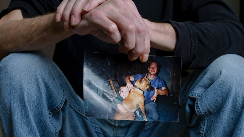 Friede holds up one of the two photos he keeps on his fridge: an image his wife snapped with his dog and 6-year-old son just after Friede was bitten by for the first time by an Egyptian cobra.