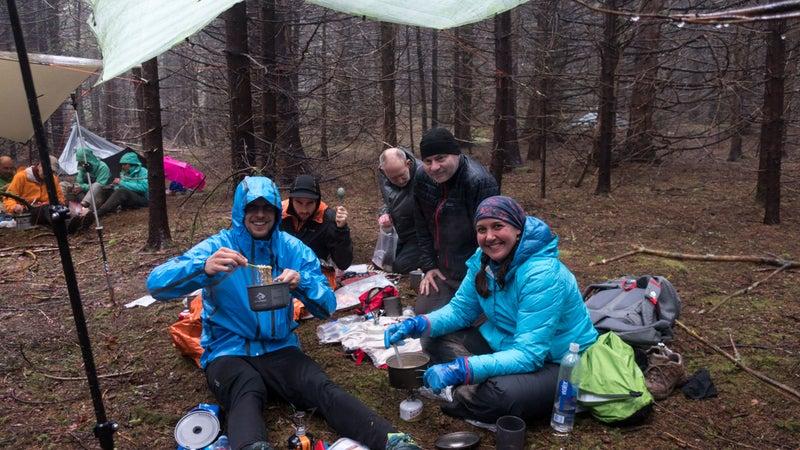 Having dinner together under group tarps