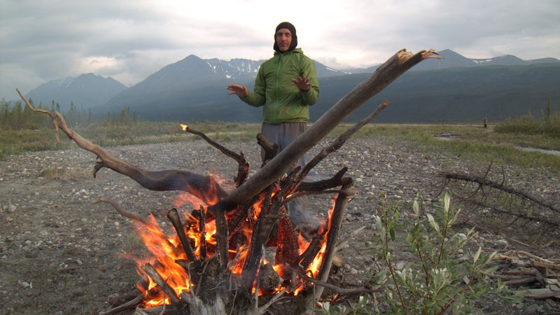 Alan warms himself over our campfire in Alaska. We'd intentionally camped on the open gravel braids, where the wind kept the mosquitoes at bay.