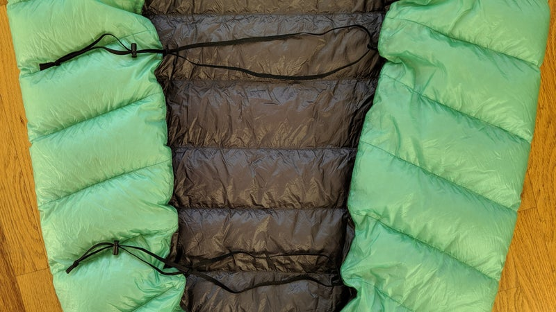 On the back of the AstraLite, there are three 3/8-inch elastcized grosgrain webbing loops. (I removed one.) A sleeping pad can be inserted into them, to create a tighter seal between the quilt and pad.
