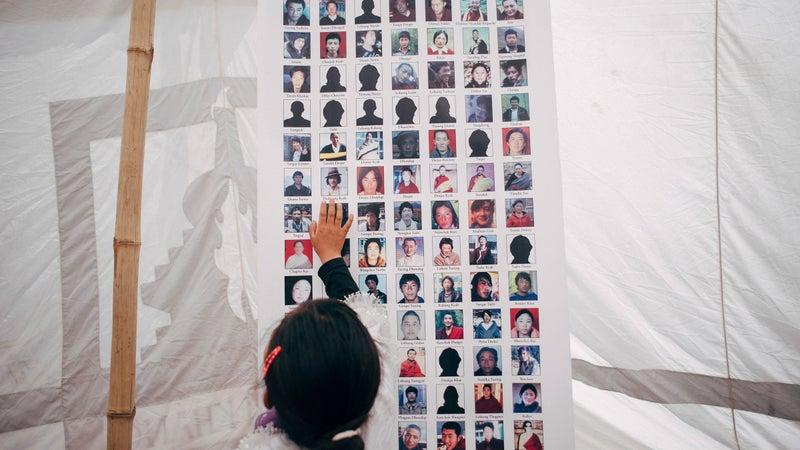 A child touching images of Tibetan self-immolators