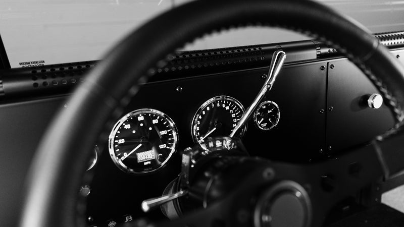 The dash has no screens and no buttons, just analog dials and manual switches. The HVAC vents run through the perforated tubes mounted under the windscreen. Rotate those towards you, or the windshield, depending on your needs.