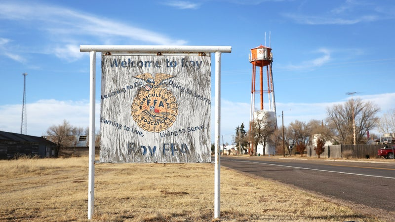 A sign welcoming you to Roy, with the iconic orange and white water tower looming in the background