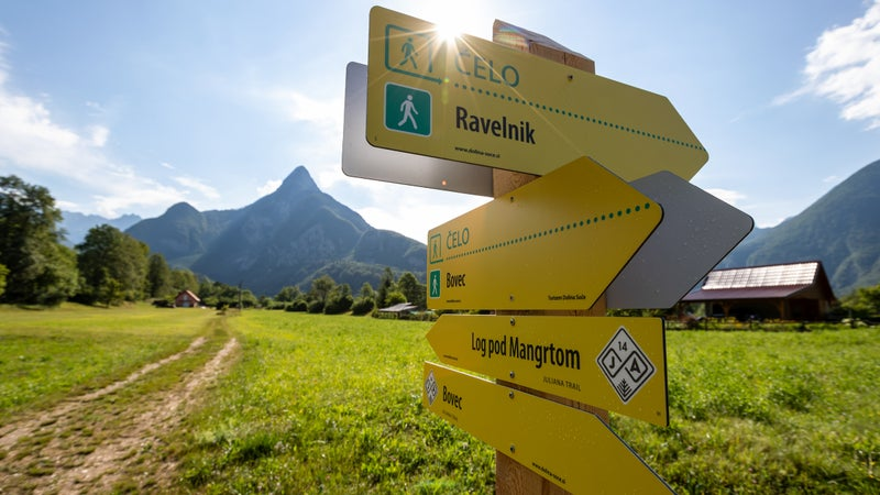 A signpost on stage 14 of the Juliana, just outside the ski town of Bovec. Mount Svinjak's iconic pyramidal summit rises in the background.