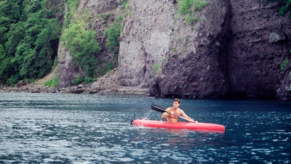 A adventure tourist enjoys kayaking in Dominica's  Scotts Head Marine Reserve. Soufriere, Dominica , Eastern Caribbean.