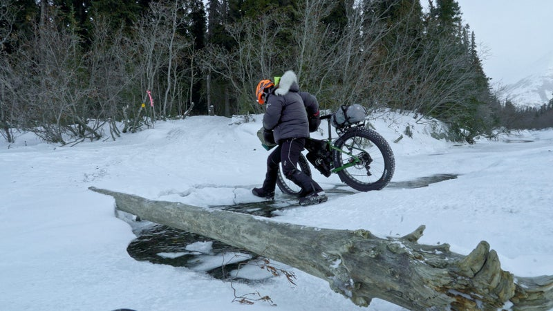 A rider navigates an open-water crossing on her way to the Rohn checkpoint in the Alaska Range.