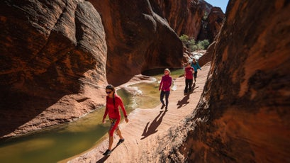 Hiking through a narrow sandstone canyon along the Red Reef Trail. Location: north of St George near Leeds, UT