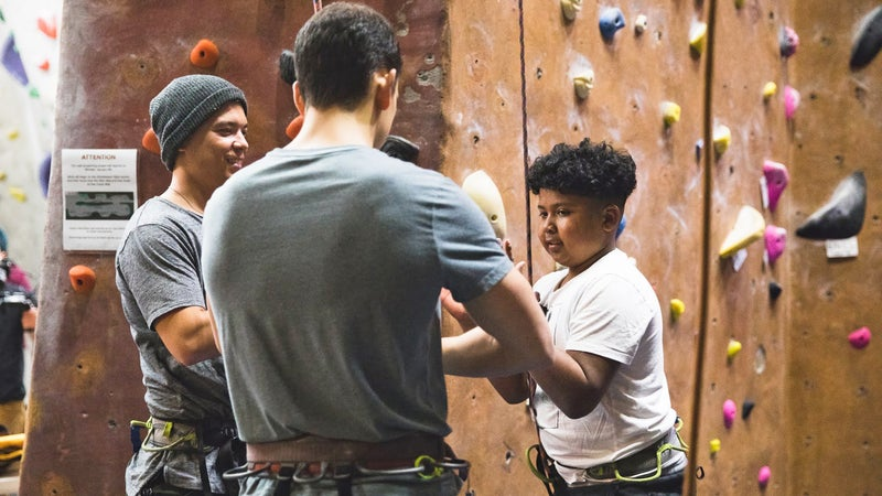 Two Brown Ascenders show a mentee how a belay device works before he climbs.