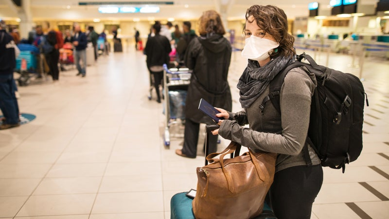 At the airport with a face mask
