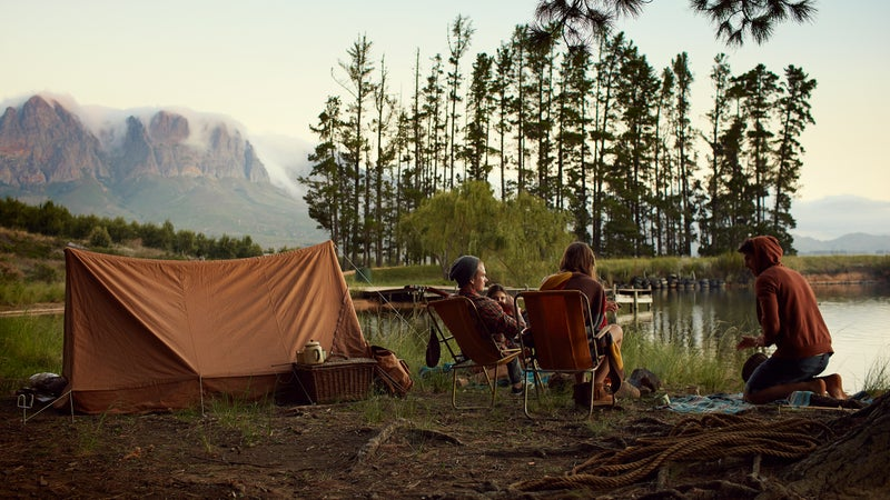 Young friends camping by lake