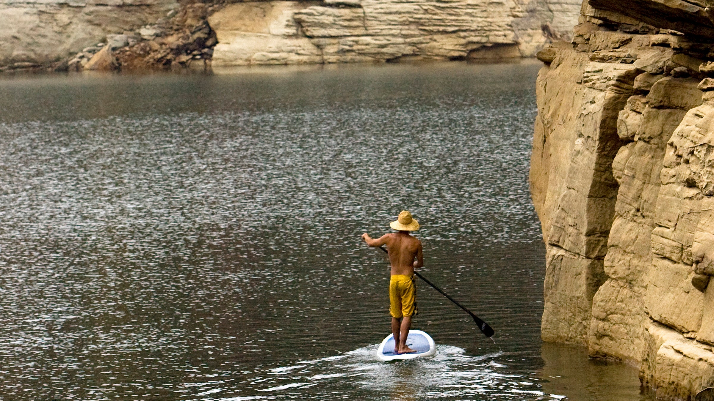 One man stand up paddleboarding on a lake under big cliffs with fall colors.