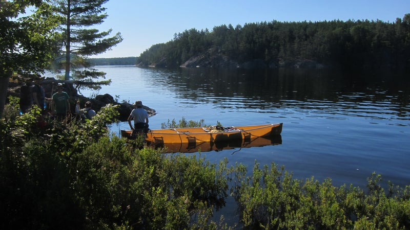 This is Souris River's Quetico 18.5. It easily fits two 100-liter packs behind the front paddler.
