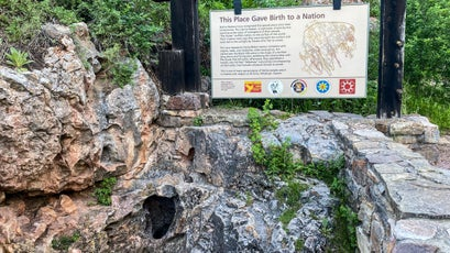 Wind Cave's natural entrance and a sign explaining its significance to the Lakota