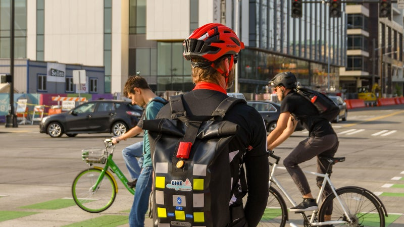 SEATTLE, WASHINGTON STATE, USA - JUNE 2018: Cyclist commuting to work in Seattle waiting at a road junction.