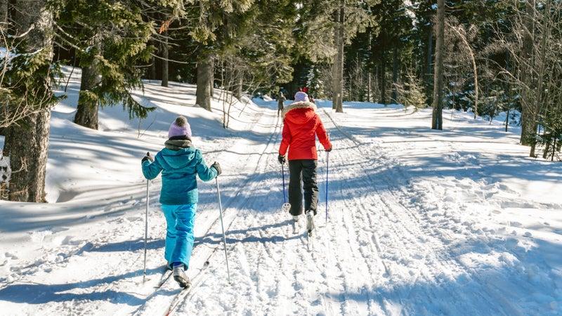 sisters in snowy winter landscape on cross-country-ski