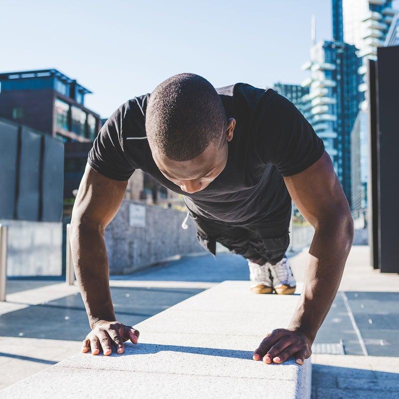 Young man exercising outdoors, doing push-ups